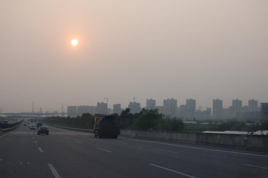 Sun through haze at 6:00 pm, with housing on the horizon